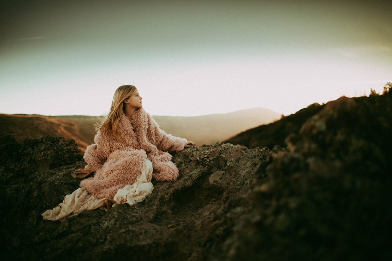 Investment Page, little girl sitting on top of a mountain in a heavy jacket